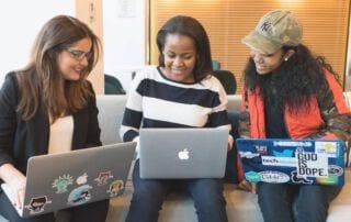 Drie vrouwen op een bank met laptops op schoot die samenwerken